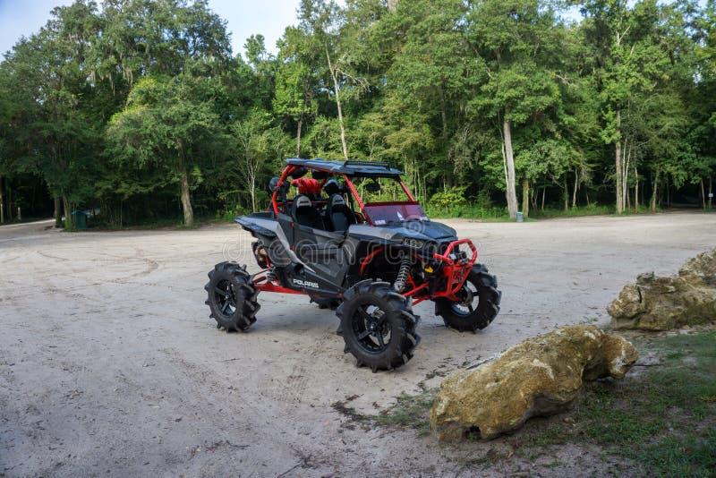 GINNIE-DE LENTES, FL DE V.S. - 1 AUGUSTUS 2018 Privé die RZR-sport zij aan zij door de kampeerauto's zich rond het natuurreservaa stock fotografie