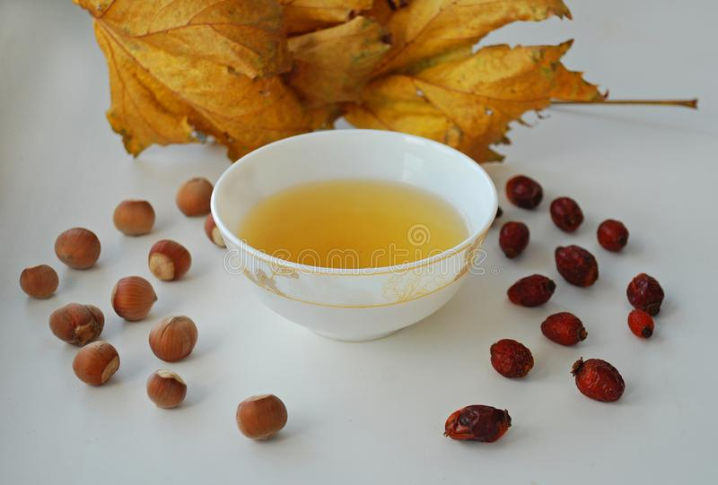 Ginseng oolong Chinese tea on a white plate with nuts, autumn leaves royalty free stock photos