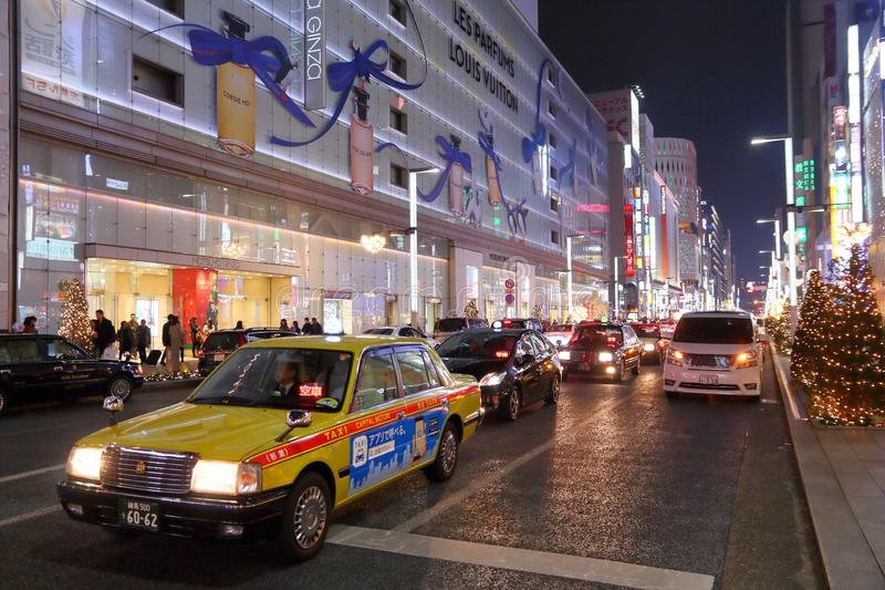 Ginza district, Tokyo. TOKYO, JAPAN - DECEMBER 4, 2016: Taxi drives in Ginza district of Tokyo, Japan. Ginza is a legendary shopping area in Chuo Ward of Tokyo stock images