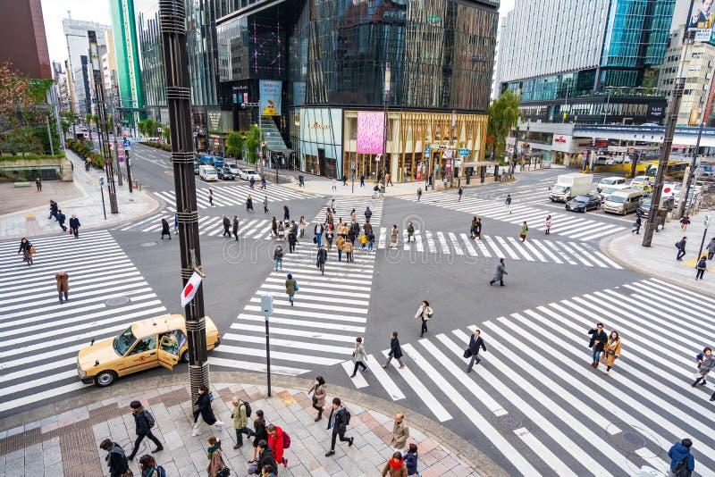Ginza, Tokyo, Japan - December 27, 2018: De mensen die van menigtevoetgangers op gestreept zebrapad bij Ginza-district in Tokyo,  stock afbeeldingen