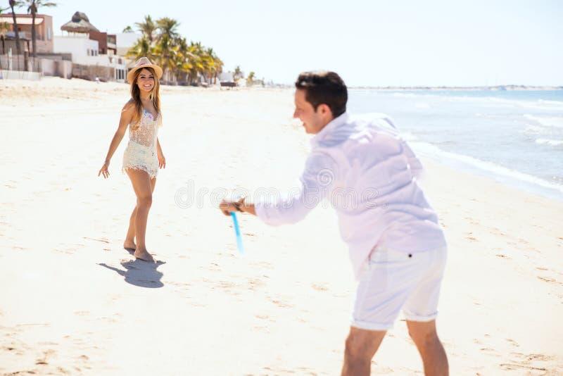 Giocando con un disco di volo alla spiaggia immagine stock