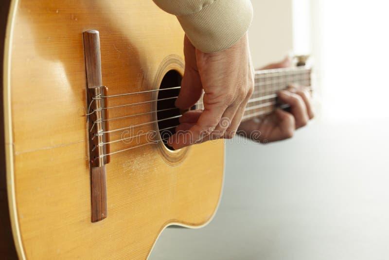 Giocando fingerpicking su una vecchia chitarra spagnola acustica nella fine su con il fuoco selettivo fotografia stock libera da diritti