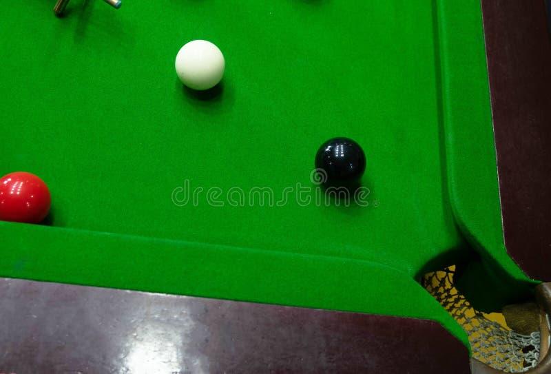 Giocando snooker, perforante la palla rossa, nero, tendente la palla ed intascante il foro per segnare i punti fotografia stock