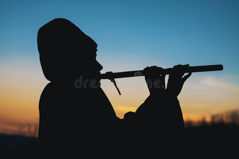 Giocando sulla siluetta di tramonto della flauto fotografia stock