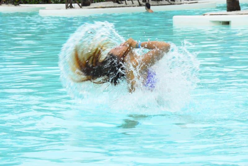 Giocando in una piscina fotografia stock