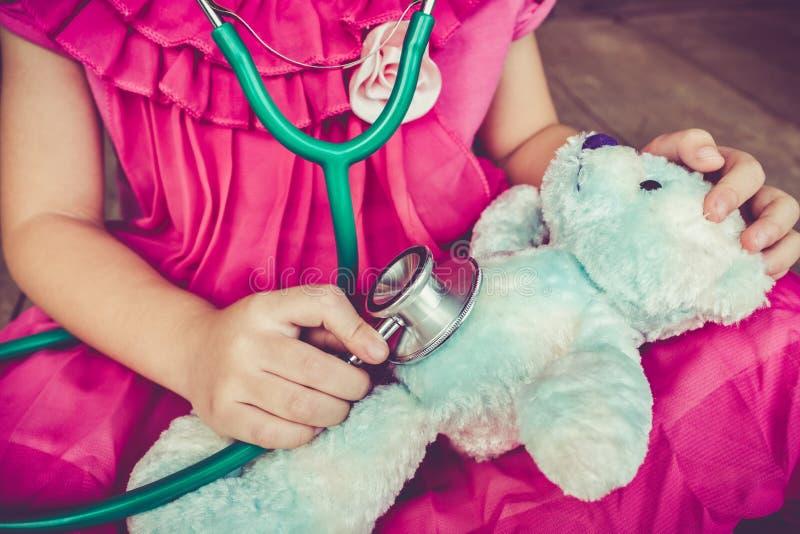 Giocar al dottoree o infermiere del bambino con l'orso del giocattolo della peluche a casa Vinta fotografia stock
