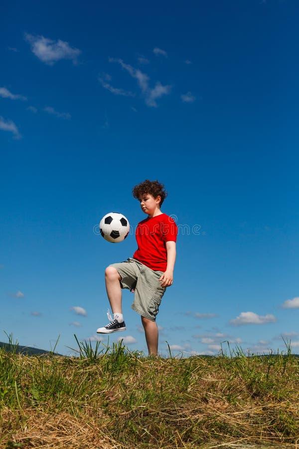 Giocar a calcioe del ragazzo all'aperto immagini stock libere da diritti
