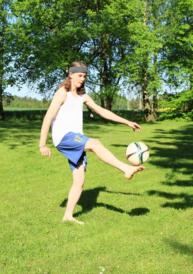 Giocar a calcioe dell'adolescente fotografia stock libera da diritti