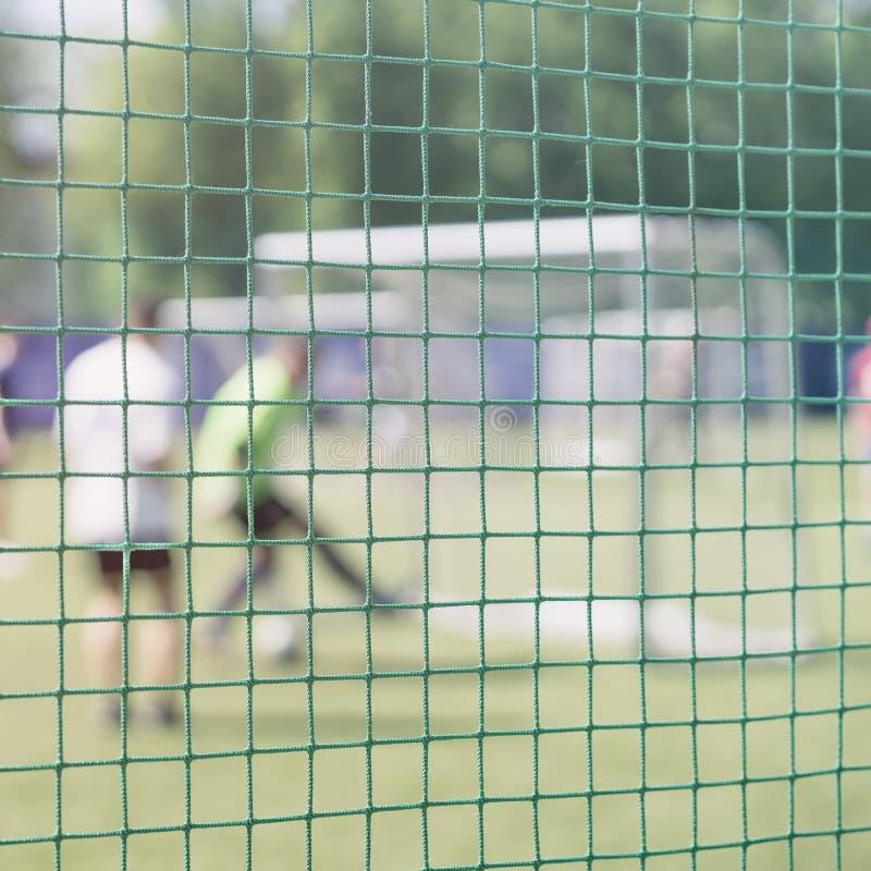 Giocar a calcioe gioco sul campo sportivo, partita di calcio sul passo Combatti per un pallone da calcio al portone di sport Calc immagini stock libere da diritti