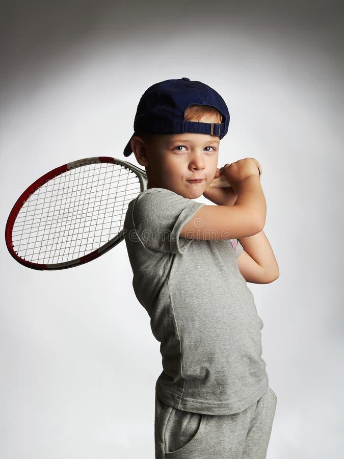 Giocar a tennise del ragazzino Bambini di sport Bambino con la racchetta di tennis immagine stock libera da diritti