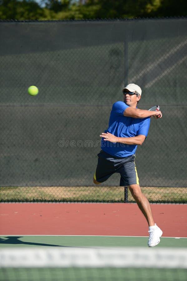 Giocar a tennise maturo dell'uomo fotografia stock