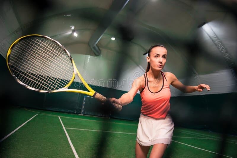 Giocar a tennise serio della giovane donna immagini stock
