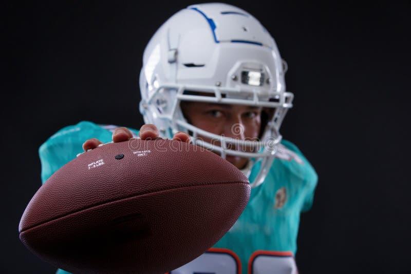 Giocatore aggressivo dello sportivo di football americano su funzionamento nero del fondo nell'azione Carta da parati di sport fotografie stock libere da diritti
