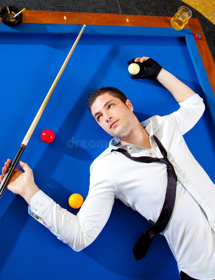Giocatore del giovane del biliardo che si trova sulla tabella dell'azzurro del raggruppamento immagine stock