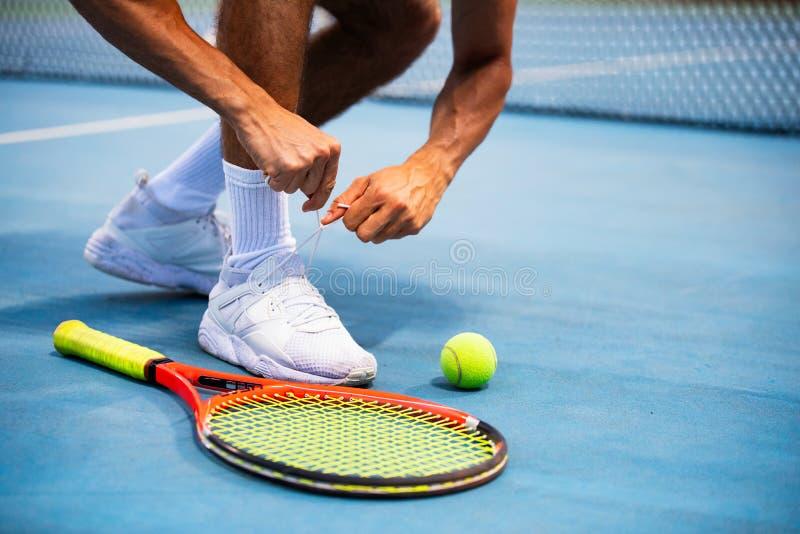 Giocatore dell'atleta di tennis che si prepara legando i laccetti durante il gioco su all'aperto immagine stock libera da diritti