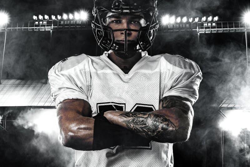 Giocatore dello sportivo di football americano in casco sullo stadio Carta da parati di sport fotografia stock libera da diritti
