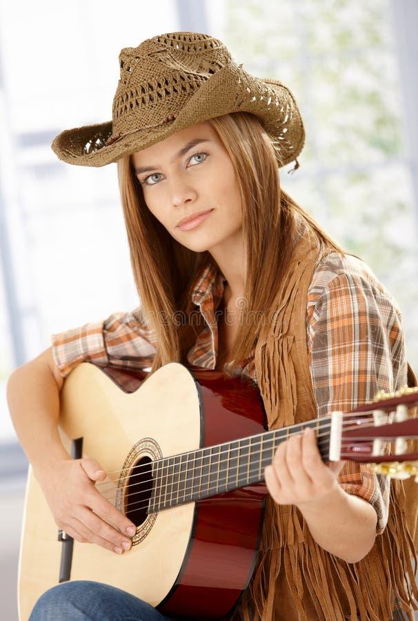 Giocatore di chitarra attraente che si esercita in cappello occidentale fotografia stock