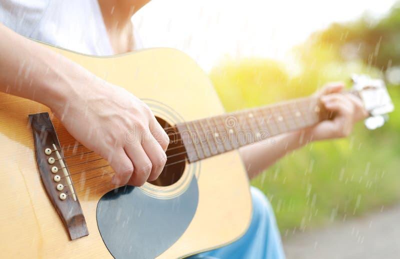 Giocatore di chitarra che gioca canzone nella pioggia di estate immagini stock libere da diritti