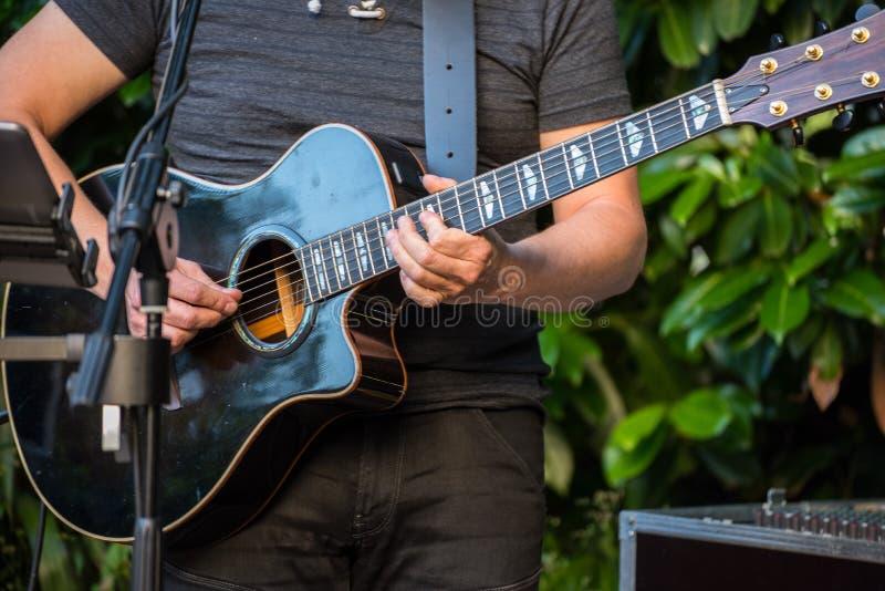 Giocatore di chitarra con la chitarra a disposizione fotografia stock