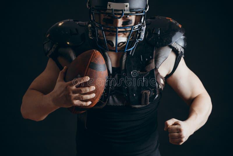 Giocatore di football americano con il casco d'uso della palla e gli schermi protettivi fotografie stock libere da diritti
