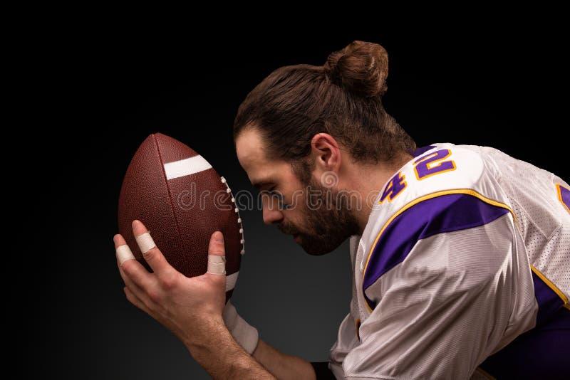 Giocatore di football americano con una palla sul momento da pregare prima del gioco immagine stock