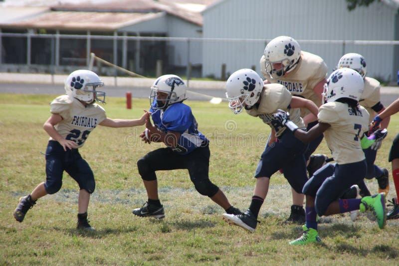 Giocatore di football americano della gioventù (10U) che esegue la palla fotografia stock