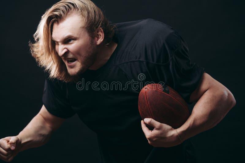 Giocatore di football americano determinato nell'azione isolato su fondo nero fotografia stock libera da diritti