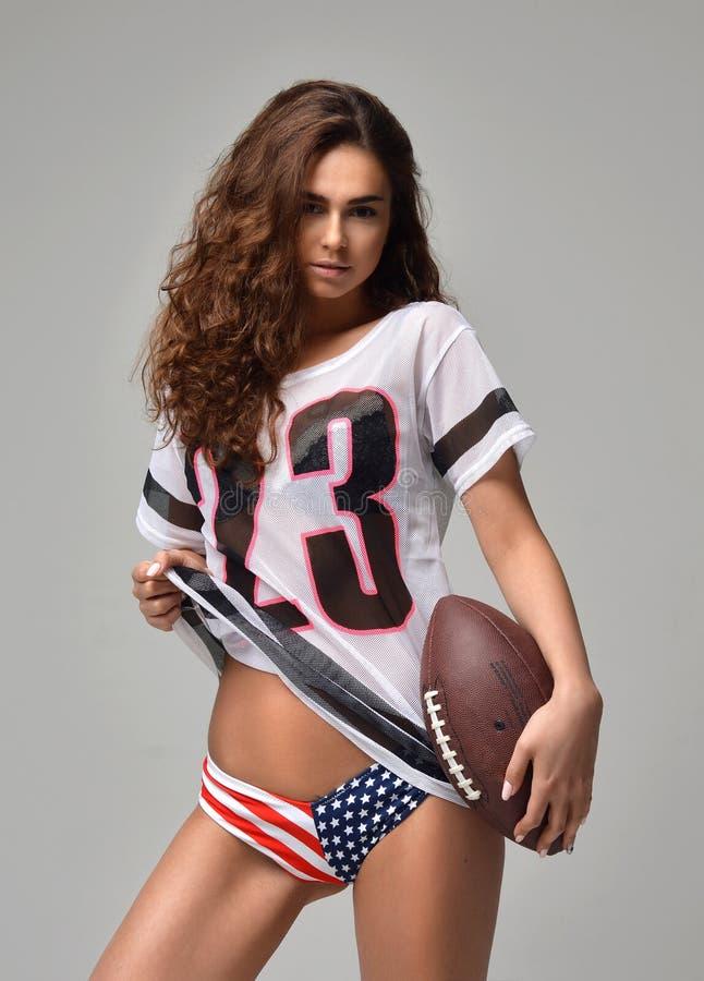 Giocatore di football americano feroce felice sexy della giovane donna con la condizione della palla fotografia stock libera da diritti