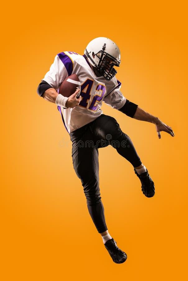 Giocatore di football americano nell'azione Salto in alto del giocatore di football americano fotografia stock libera da diritti