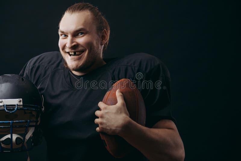Giocatore di football americano sicuro nel casco e nella palla neri della tenuta di sportwear immagine stock libera da diritti
