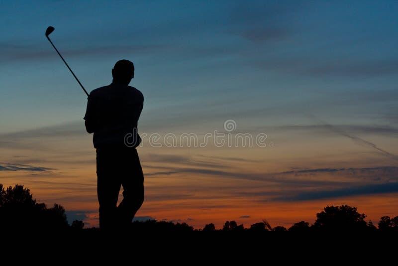 Giocatore di golf che colloca sul tee fuori al crepuscolo fotografie stock