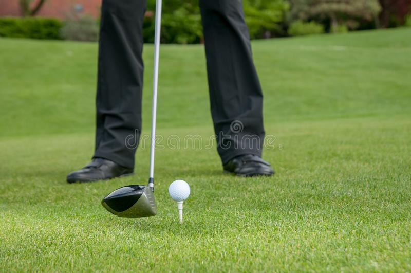 Giocatore di golf che colloca sul tee fuori sul campo da golf fotografia stock libera da diritti