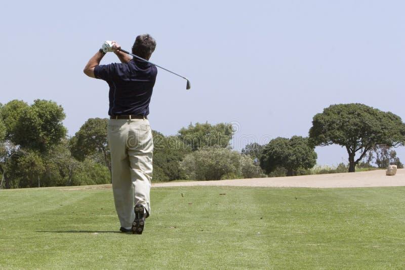 Giocatore di golf che fa il colpo del tratto navigabile fotografia stock