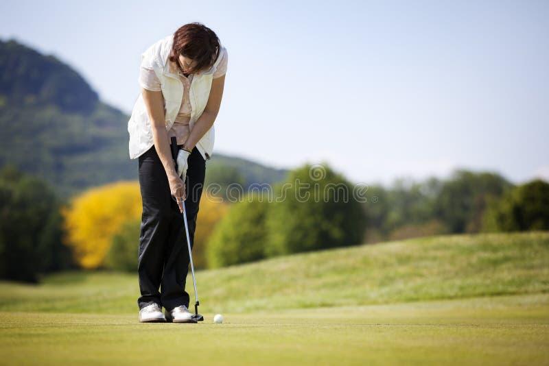 Giocatore di golf che mette sfera. immagini stock