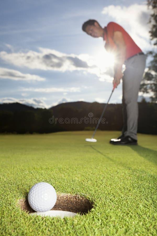 Giocatore di golf che mette sfera nella tazza. fotografia stock