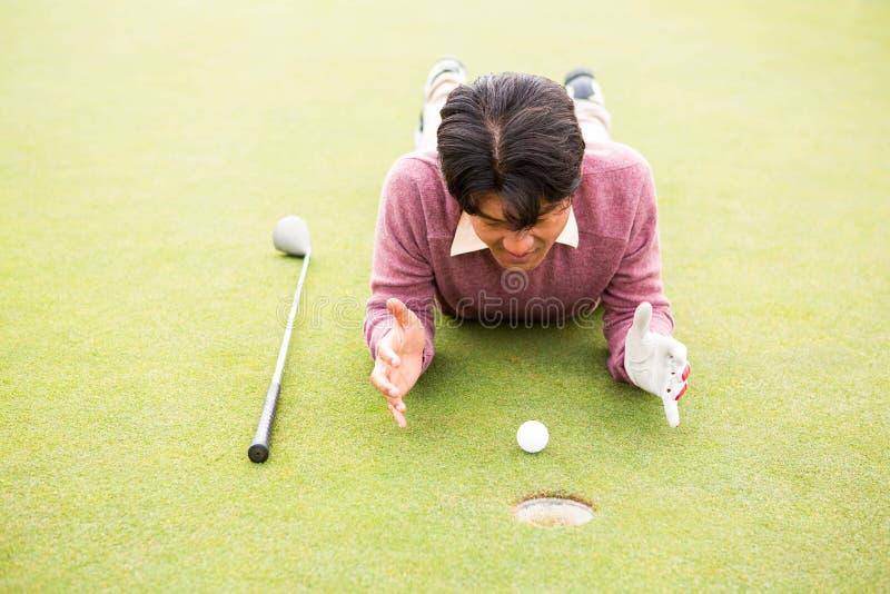 Giocatore di golf che si trova vicino alla palla da golf immagini stock