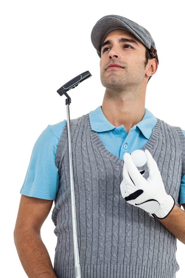 Giocatore di golf che sta con la palla da golf ed il club di golf immagini stock
