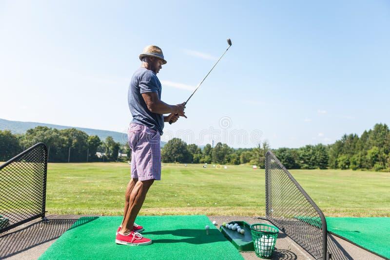 Giocatore di golf che un a Tire in su fotografia stock libera da diritti