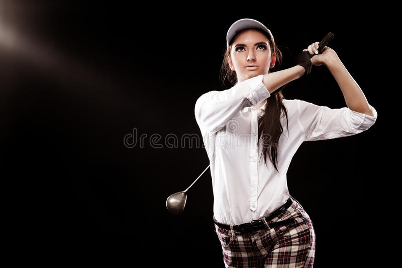 Giocatore di golf della donna che colpisce la palla isolata su fondo nero Copi lo spazio Concetto dell'annuncio immagini stock