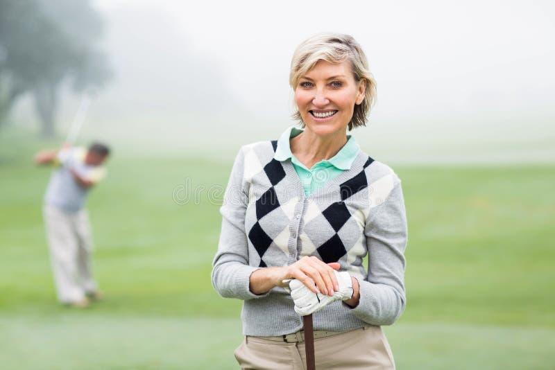 Giocatore di golf di signora che sorride alla macchina fotografica con il partner dietro fotografia stock