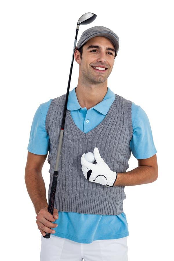 Giocatore di golf felice che sta con la palla da golf ed il club di golf fotografia stock