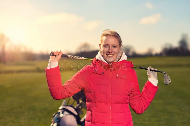 Giocatore di golf femminile con un club di golf sopra la sua spalla fotografia stock