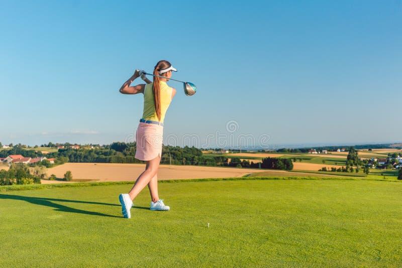 Giocatore di golf femminile professionale che sorride mentre oscillando un club del driver immagini stock