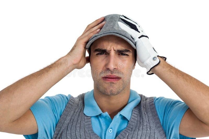 Giocatore di golf frustrato che sta sul fondo bianco fotografia stock