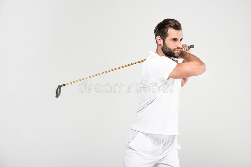 giocatore di golf maschio in abiti sportivi bianchi con il club di golf, immagini stock