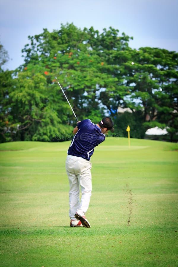 Giocatore di golf maschio asiatico sul terreno da golf immagine stock