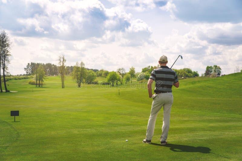 Giocatore di golf maschio che sta al tratto navigabile sul campo da golf fotografia stock libera da diritti