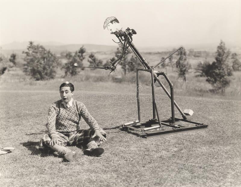 Giocatore di golf meccanico circa per colpire palla da golf fuori dalla testa dell'uomo immagini stock libere da diritti