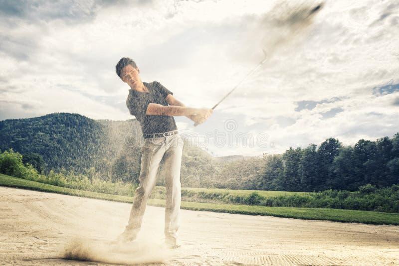Giocatore di golf nel separatore di sabbia. fotografie stock libere da diritti