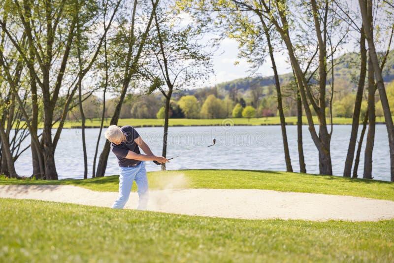 Giocatore di golf senior che gioca dal bunker fotografie stock